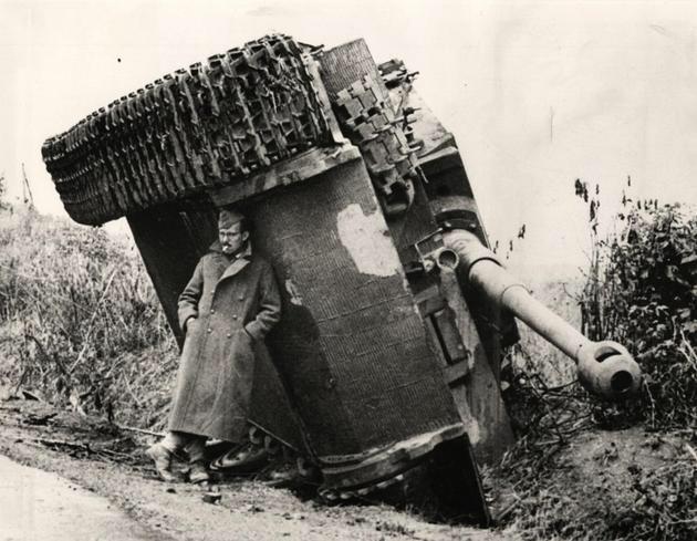 """944年,意大利,一个英国士兵在一辆侧翻的虎式坦克下躲雨"""""""
